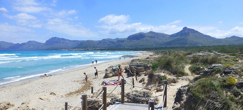 Imagen de playa de arena con mar azul turquesa y montaña en el fondo